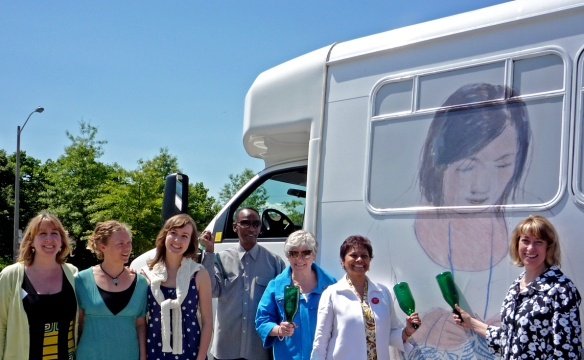 Local leaders and project coordinators christen an art-wrapped vehicle at the Art on the Move launch.